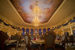 """Decorated with a coffered, 20-foot ceiling with fluffy clouds and cherubs, the ballroom at Be Our Guest Restaurant features sparkling chandeliers designed to convey the elegance of the Beast's Castle in """"Beauty and the Beast."""" Located in Magic Kingdom, the stylish restaurant will serve French-inspired cuisine for quick-service lunch and table-service dinner. Be Our Guest Restaurant is part of New Fantasyland at Walt Disney World Resort in Lake Buena Vista, Fla. (Matt Stroshane, photographer)"""